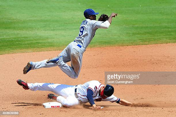Dee Gordon of the Los Angeles Dodgers turns a seventh double play against Andrelton Simmons of the Atlanta Braves at Turner Field on August 14, 2014...