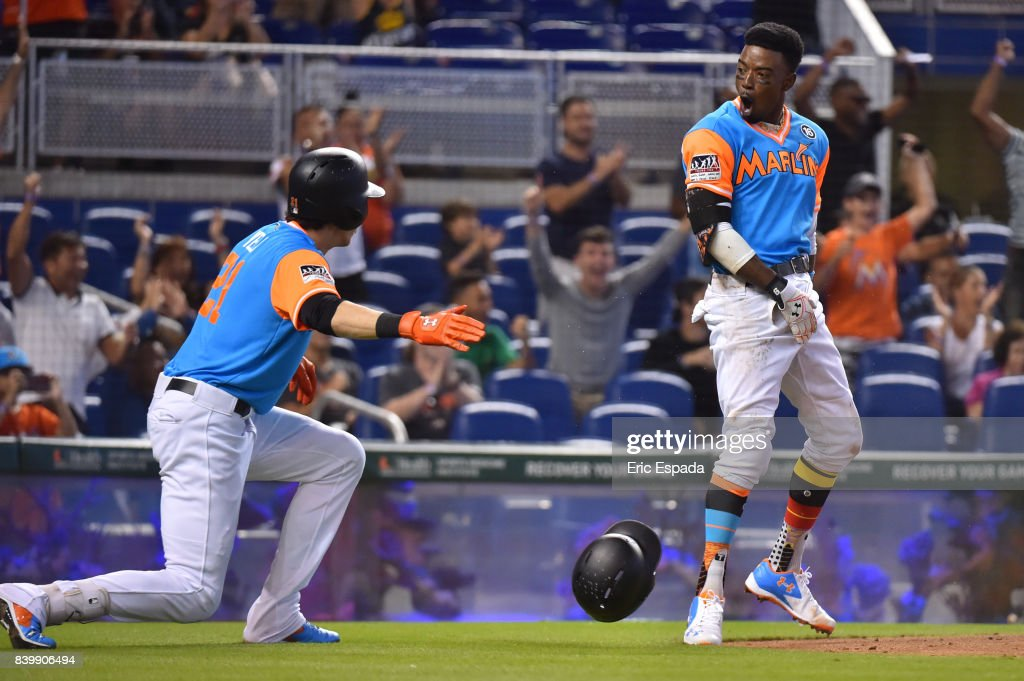 Dee Gordon #9 of the Miami Marlins celebrates with Christian Yelich #21 after scoring a run in the third inning against the San Diego Padres at Marlins Park on August 27, 2017 in Miami, Florida.