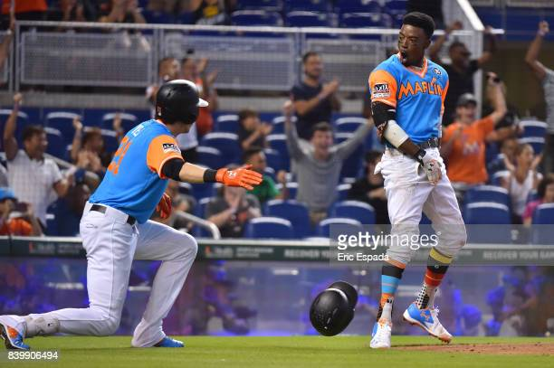 Dee Gordon of the Miami Marlins celebrates with Christian Yelich after scoring a run in the third inning against the San Diego Padres at Marlins Park...