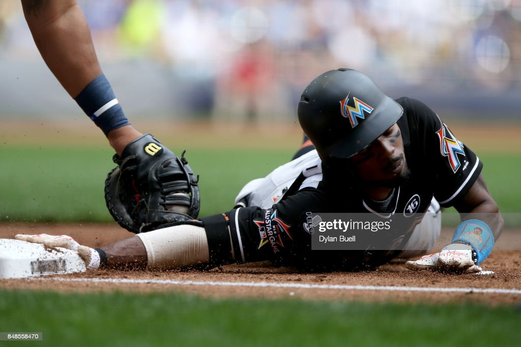 Dee Gordon #9 of the Miami Marlins dives back into first base past the tag of Jesus Aguilar #24 of the Milwaukee Brewers during a pickoff attempt in the first inning at Miller Park on September 17, 2017 in Milwaukee, Wisconsin.