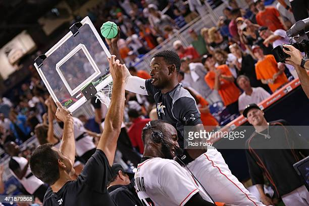 Dee Gordon of the Miami Marlins dunks a toy basketball over Marcell Ozuna after the Marlins' walkoff victory in the game against the Philadelphia...