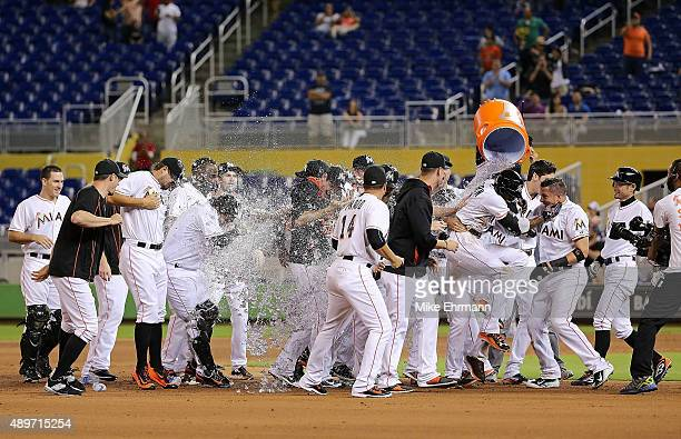 Dee Gordon of the Miami Marlins is congratulated after hitting a walkoff double in the 11th inning during a game against the Philadelphia Phillies at...