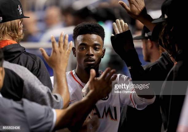 Dee Gordon of the Miami Marlins is congratulated after scoring in the second inning during a game against the Atlanta Braves at Marlins Park on...