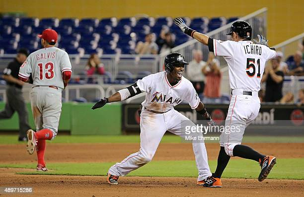 Dee Gordon of the Miami Marlins is congratulated by Ichiro Suzuki after hitting a walkoff double in the 11th inning during a game against the...