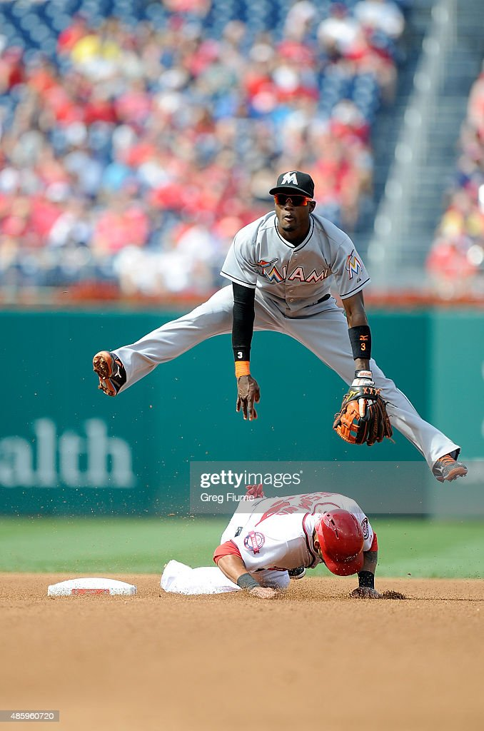 Dee Gordon #9 of the Miami Marlins jumps over Ian Desmond #20 of the Washington Nationals after completing a double play in the fourth inning at Nationals Park on August 30, 2015 in Washington, DC.