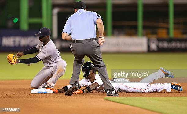 Dee Gordon of the Miami Marlins slides into second base after hitting a double as Didi Gregorius of the New York Yankees can't hold on to the ball...