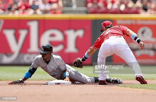 Dee Gordon of the Miami Marlins slides safely ahead of the tag of Eugenio Suarez of the Cincinnati Reds for a stolen base in the 1st inning at Great...