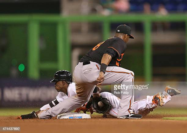 Dee Gordon of the Miami Marlins slides safely into second base under the tag of Jimmy Paredes of the Baltimore Orioles during the game at Marlins...