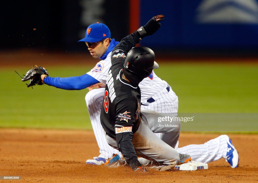 Dee Gordon #9 of the Miami Marlins steals second base in the third inning ahead of the tag from Neil Walker #20 of the New York Mets at Citi Field on April 7, 2017 in the Flushing neighborhood of the Queens borough of New York City.