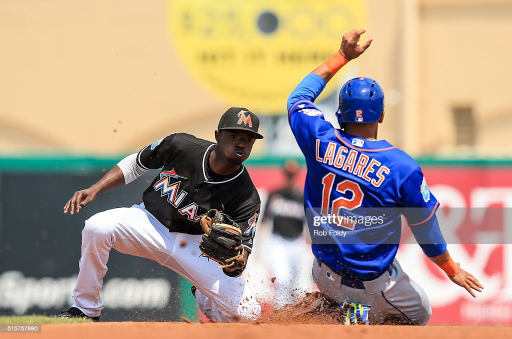 Dee Gordon #9 of the Miami Marlins tags out Juan Lagares #12 of the New York Mets during the first inning of the spring training game on March 15, 2016 in Jupiter, Florida.