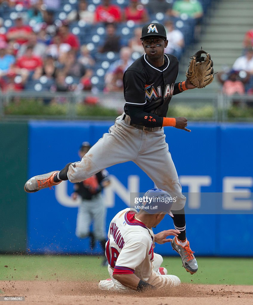 Dee Gordon #9 of the Miami Marlins tries to turn a double play against Cesar Hernandez #16 of the Philadelphia Phillies in the bottom of the seventh inning at Citizens Bank Park on September 18, 2016 in Philadelphia, Pennsylvania. The Marlins defeated the Phillies 5-4.