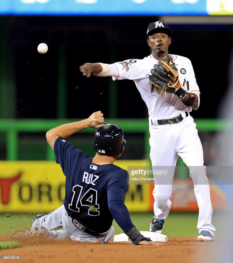 Dee Gordon #9 of the Miami Marlins turns a double play as Rio Ruiz #14 of the Atlanta Braves slides into second during a game at Marlins Park on September 29, 2017 in Miami, Florida.