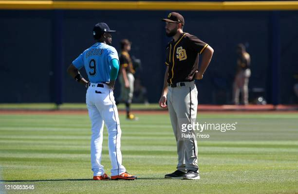 Dee Gordon of the Seattle Mariners and Eric Hosmer of the San Diego Padres meet in the outfield prior to a Cactus League spring training baseball...