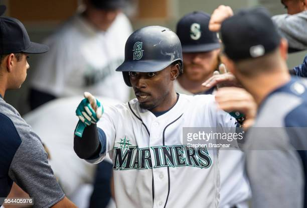Dee Gordon of the Seattle Mariners celebrates in the dugout after scoring a run on a hit by Robinson Cano off of starting pitcher Sean Manaea of the...