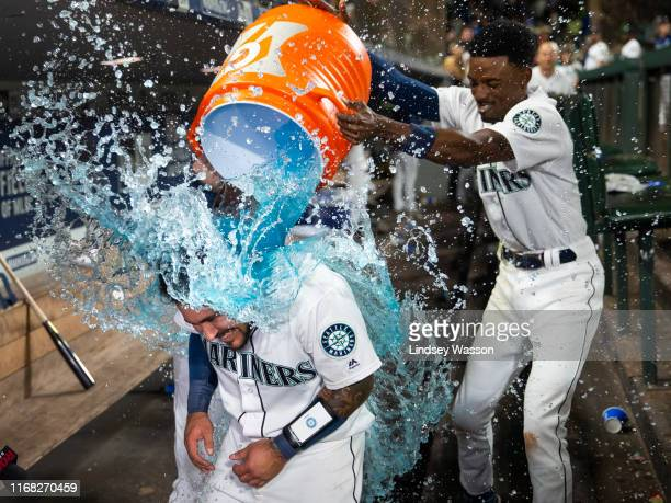 Dee Gordon of the Seattle Mariners drops Gatorade on Omar Narvaez after he hit a walk-off home run against the Chicago White Sox at T-Mobile Park on...