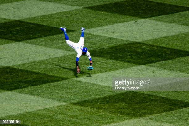 Dee Gordon of the Seattle Mariners flies through the air after making a long throw to third base on a single by Luis Valbuena of the Los Angeles...