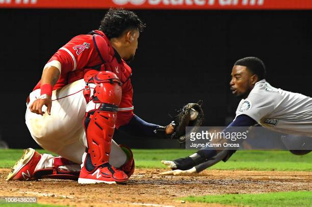 Dee Gordon of the Seattle Mariners is called out at home on a tag by Jose Briceno of the Los Angeles Angels of Anaheim in the tenth inning at Angel...