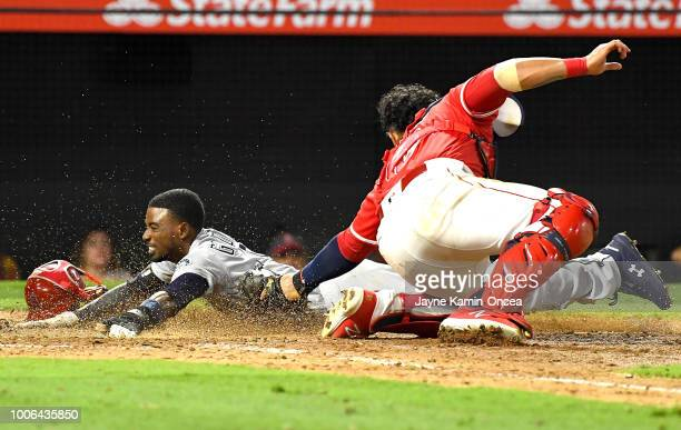 Dee Gordon of the Seattle Mariners is called out at home on a tag Jose Briceno of the Los Angeles Angels of Anaheim in the tenth inning at Angel...