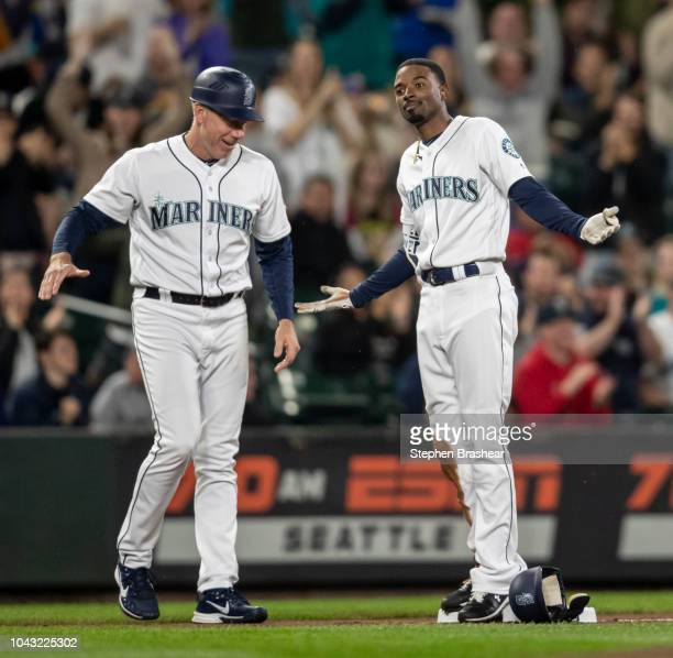 Dee Gordon of the Seattle Mariners reacts as third base coach Scott Brosius celebrates after Gordon hit a RBItriple off of starting pitcher Adrian...