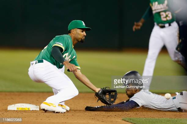Dee Gordon of the Seattle Mariners safely steals second base ahead of the tag from Marcus Semien of the Oakland Athletics in the top of the sixth...