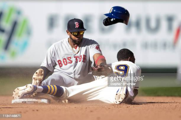 Dee Gordon of the Seattle Mariners steals second base as he collides with shortstop Xander Bogaerts of the Boston Red Sox during the seventh inning...