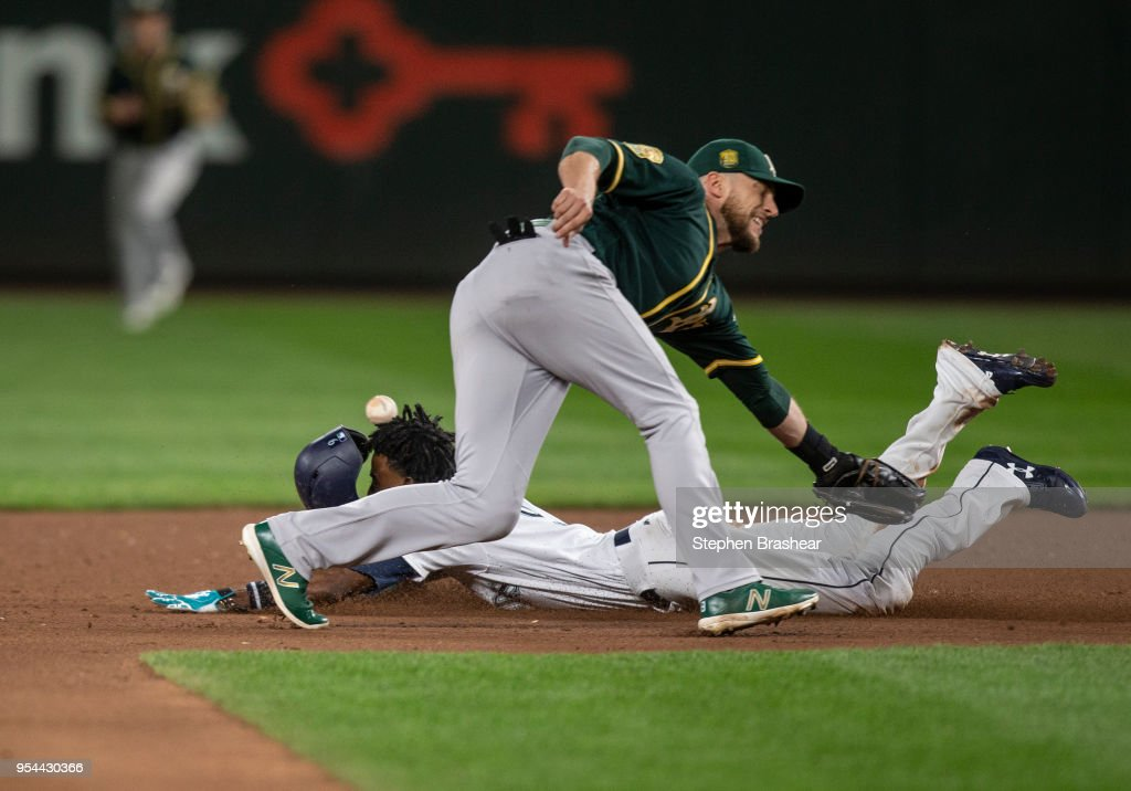 Dee Gordon #9 of the Seattle Mariners steals second base as second baseman Jed Lowrie #8 of the Oakland Athletics cannot hold on to the ball during the seventh inning of a game at Safeco Field on May 3, 2018 in Seattle, Washington. The Mariners won the game 4-1.