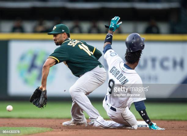 Dee Gordon of the Seattle Mariners steals second base before shortstop Marcus Semien of the Oakland Athletics can make a tag during the first inning...