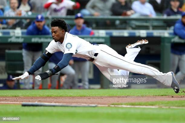 Dee Gordon scores on a sacrifice fly by Jean Segura of the Seattle Mariners in the first inning against the Texas Rangers during their game at Safeco...