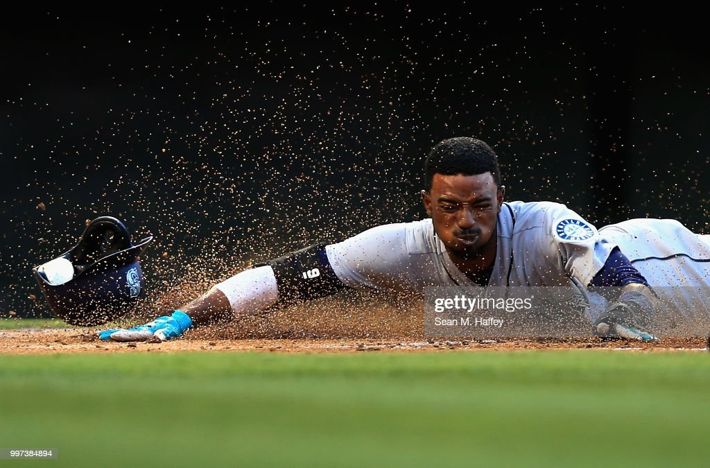 Dee Gordon #9 slides safely at home scoring on an RBI single hit by Kyle Seager #15 of the Seattle Mariners during the first inning of a game against the Los Angeles Angels of Anaheim at Angel Stadium on July 12, 2018 in Anaheim, California.