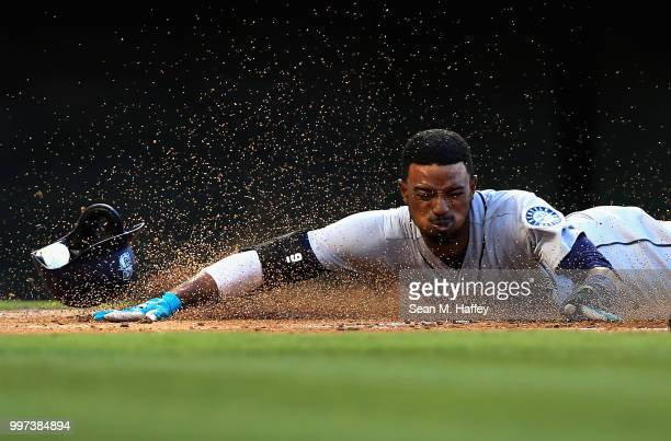 Dee Gordon slides safely at home scoring on an RBI single hit by Kyle Seager of the Seattle Mariners during the first inning of a game against the...