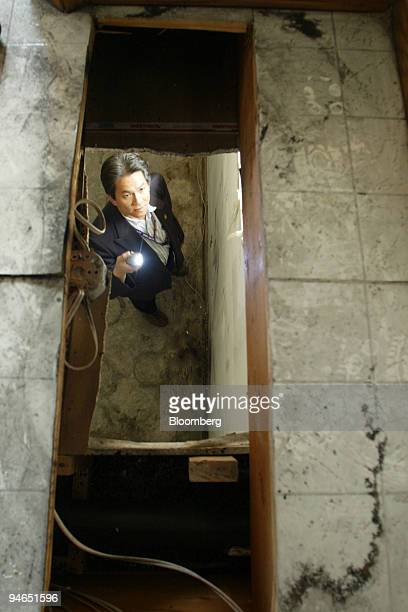 Dee Nguyen realtor inspects a hole has been cut through the floor of the kitchen pantry in order accommodate marijuana growing inside this home in...