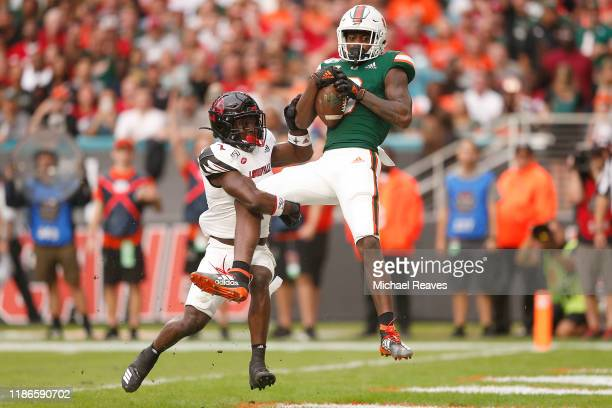 Dee Wiggins of the Miami Hurricanes catches a touchdown pass against the Louisville Cardinals during the first half at Hard Rock Stadium on November...