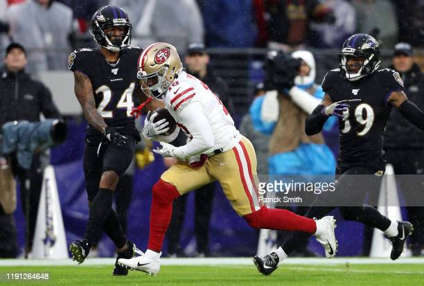Deebo Samuel of the San Francisco 49ers catches a 33-yard touchdown pass against Marcus Peters and Brandon Carr of the Baltimore Ravens during the...