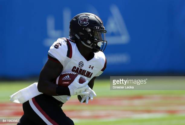 Deebo Samuel of the South Carolina Gamecocks runs back the opening kickoff for a touchdown against the North Carolina State Wolfpack during their...