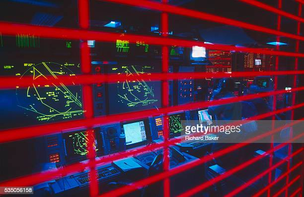 Deep belowdecks we peer through a striped window of the highlyclassified Conflict Direction Center or War Room on the aircraft carrier US Navy USS...