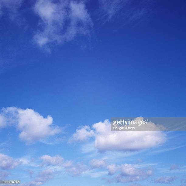 Deep blue sky with white clouds in distance.