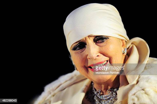 A deep closeup of refined Valentina Cortese looking to her left side wearing her inseparable symbolic white headscarf and a precious chocker around...