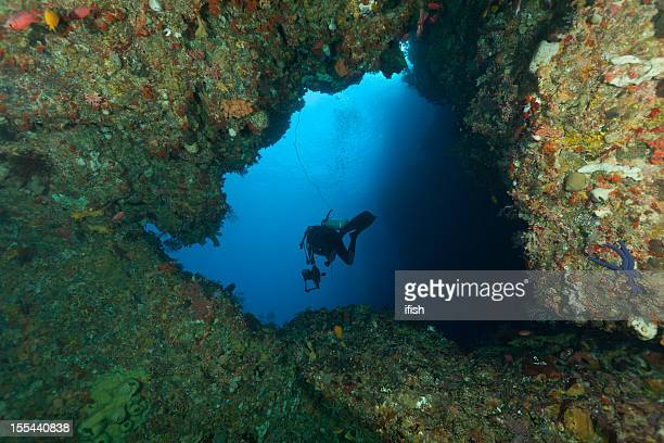 deep down, cave-diver leaves a cave, west coast alor, indonesia - squirrel fish stock photos and pictures