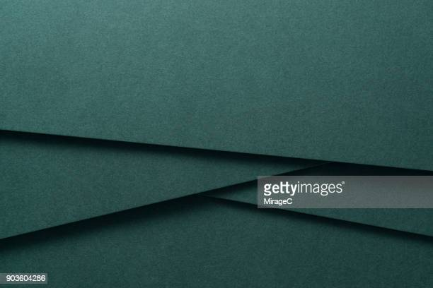 deep green colored paper crossing - abstract pattern stock-fotos und bilder