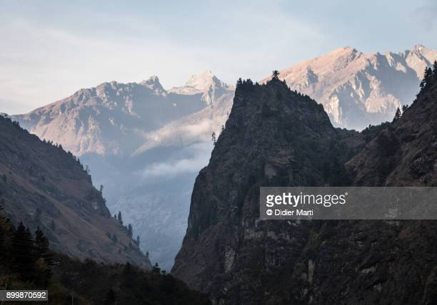 deep valley at sunset in the annapurna mountain range along the famous annapurna circuit trekking in nepal - didier marti stock photos and pictures