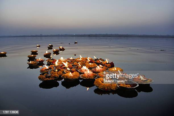 deepak in the ganges river. the deepak or oil lamps are used as an offering to the ganges river or great mother at sunrise and sunset in respect of mother goddess ganges, god shiva and the rising sun. varanasi, india. - ganges river stock pictures, royalty-free photos & images