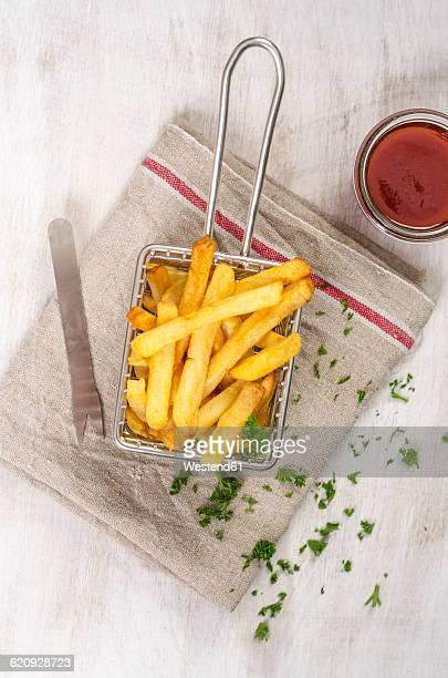 Deep-fried french fries in chip basket, ketchup