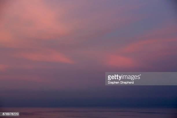 deeply coloured clouds and sky at sunset over the sea looking to the horizon. - ilfracombe stock photos and pictures