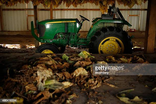 A Deere Co John Deere 5055D utility tractor sits parked in a barn as migrant workers hang Burley tobacco grown by Langley Farms in Finchville...