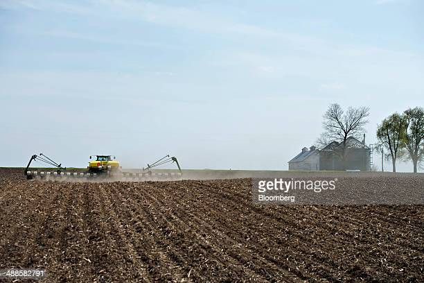 A Deere Co John Deere 8130 tractor pulls a 24row planter as corn is planted in Malden Illinois US on Tuesday May 6 2014 This year's record advance in...