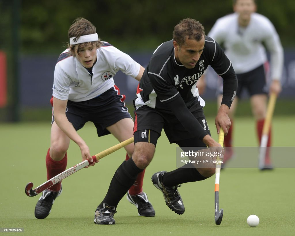 Deeside's Trevor Merrick is closed down by Brooklands MU's David Flanagan (left) during their promotion tournament game at Cannock Hockey Club, Cannock.