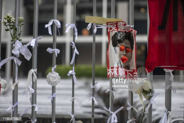 A defaced poster depicting Hong Kong Chief Executive Carrie Lam hangs on a fence outside the Central Government Offices in Hong Kong China on Tuesday...