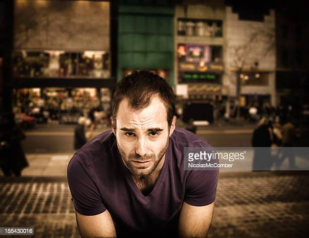 Defeated man in urban setting