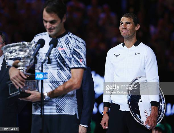 A defeated Raphael Nadal of Spain reacts as Roger Federer of Switzerland celebrates with the Trophy after winning in the Men's Final match against on...