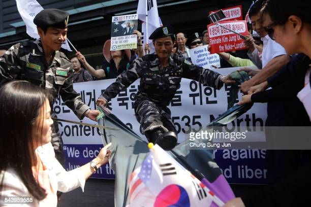 Defectors from North Korea now living in South Korea tear a portrait of North Korean leader Kim JongUn during a rally on September 8 2017 in Seoul...